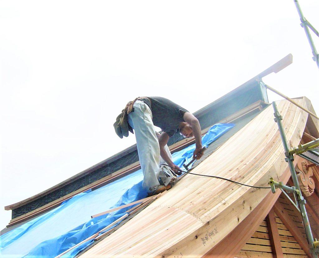 急勾配の屋根の上で踏ん張って仕事